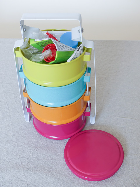 brightly coloured 4 tier tiffin box with top layer open