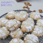 tray of amaretti biscuits with almonds and amaretto liqueur in the background