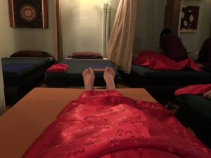 person laying flat on bed in a dimly lit room covered with red sheet with toes poking out the end