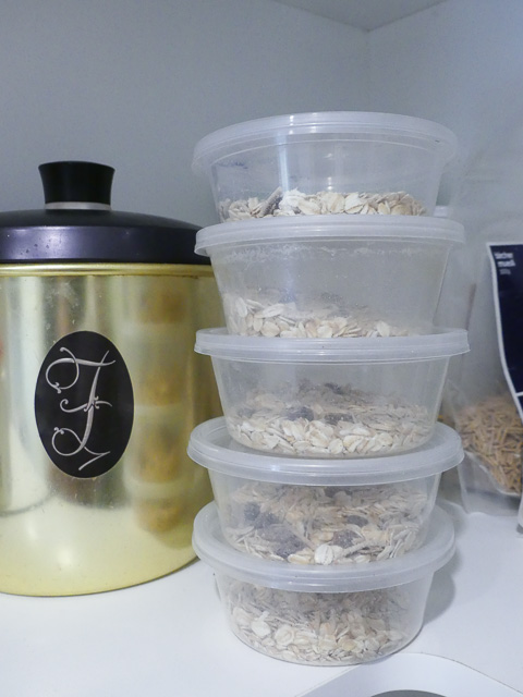 stack of round plastic containers filled with muesli beside an aluminium storage container with a 'F' monogram