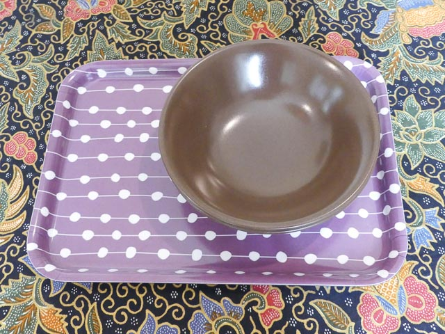 two brown bowls sit on a small purple and white tray