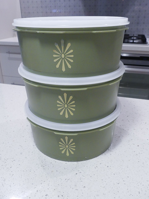 three green platic tupperware containers with yello starburst motif sit stacked on a bench
