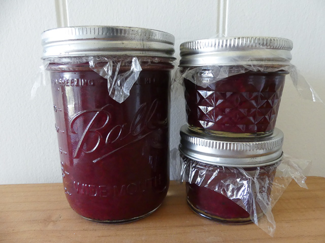 three jars of purple plum and ginger relish stacked on a table