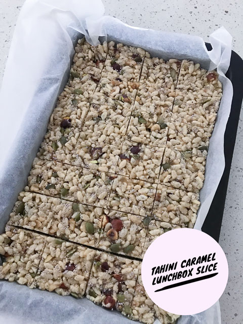baking tray of tahini caramel puffed rice slice cut into squares