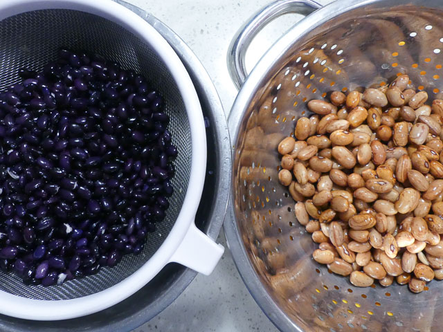 two colanders with black beans and borlotti beans