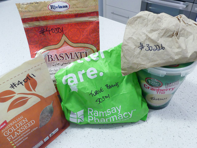 various plastic and paper bags filled with dry pantry goods