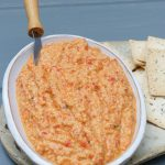 shallow dish of cashew & red pepper dip with small knife in dish and crackers alongside