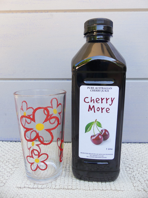 large glass with floral print beside a large plastic bottle of cherry juice