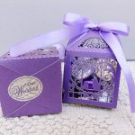 two purple cardboard boxes with cut out morifs and purple ribbons tied on top