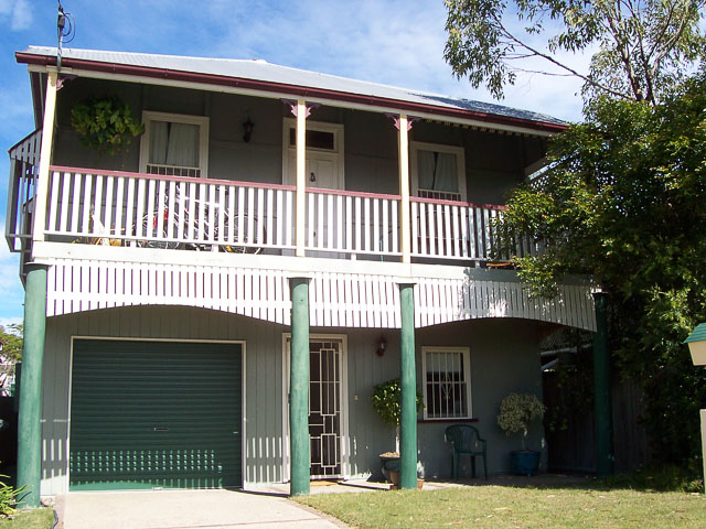 large wooden Queenslander house with iron roof and wooden balcony