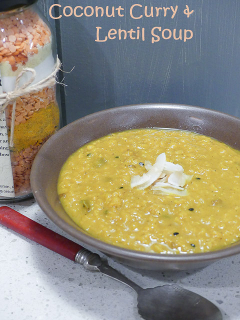 coconut curry and lentil soup in brown bowl sitting on bench alongside spoon and jar of lentils and spices
