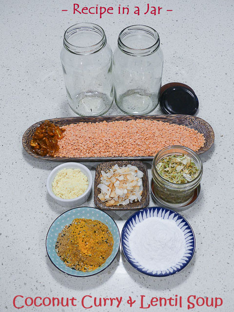two glass jars on bench with glass jars, assorted spices and lentils in various dishes