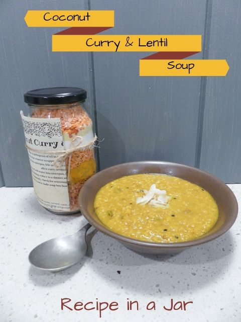 glass jar filled with lentils and spices on bench beside brown bowl of curry coconut and lentil soup