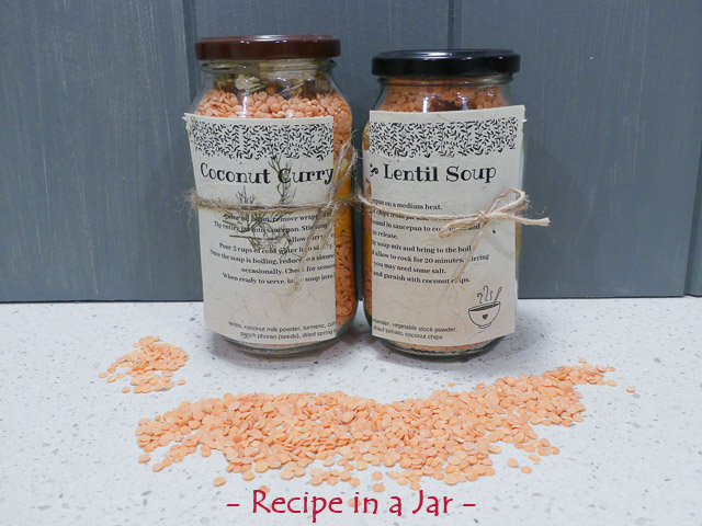 two glass jars filled with lentils and spices on a bench with red lentils scattered in front
