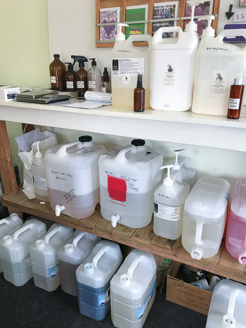 large plastic containers with taps filled with cleaning products stacked onto shelves at Vessel Nundah