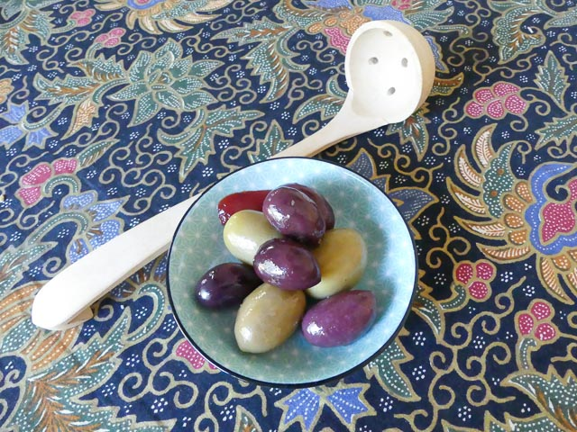 blue ceramic bowl of green and purple olive with wooden olive strainer alongside