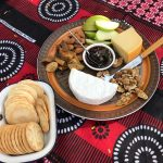 cheese plate with fruit, nuts and crackers on a bold printed table cloth