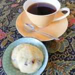 cranberry & coconut biscuits in a green dish beside an orange cup and saucer filled with coffee