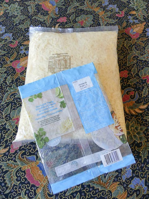 large platic bag of grated cheese with smaller plastic bag resting on top