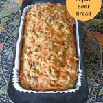 baking tin containing crusty beer bread with cheese & pepita topping