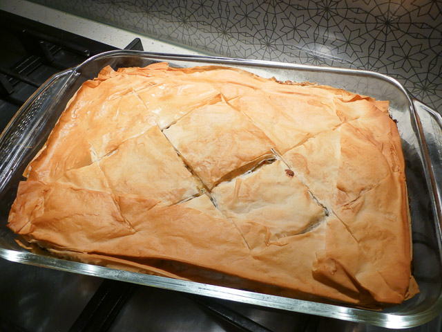 glass dish of spanokopita pie with crisp brown filo pastry top