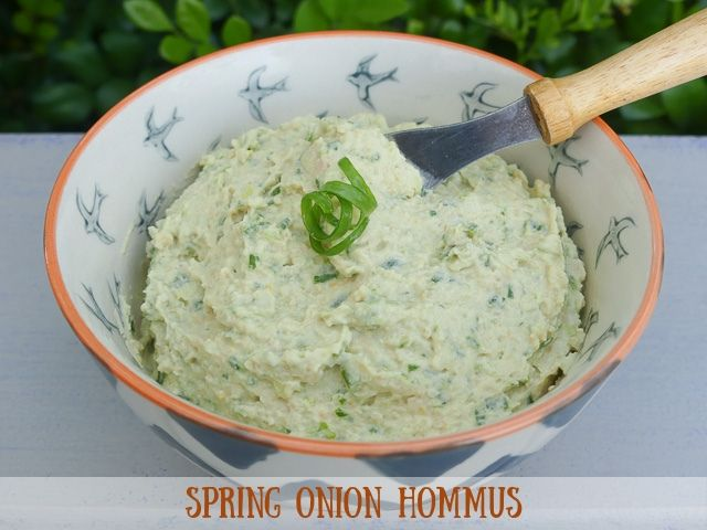 bowl of spring onion hommus with small knife in hommus