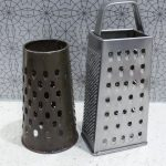 one round grater and one box grater sit on a bench